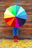 Γυναίκα φωτογραφιών φθινοπώρου που κρατά τη ζωηρόχρωμη φθορά ομπρελών κόκκινες λαστιχένιες μπότες πέρα από το ξύλινο υπόβαθρο Στοκ εικόνα με δικαίωμα ελεύθερης χρήσης