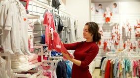 Γυναίκα, χειρωνακτική στάση εξέτασης με την ένδυση παιδιών ` s στο κατάστημα απόθεμα βίντεο