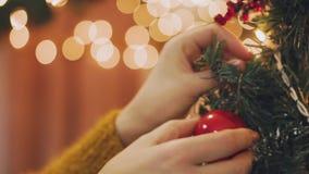 Γυναίκα χεριών που διακοσμεί στο χριστουγεννιάτικο δέντρο με τα φω'τα πυράκτωσης Χριστουγέννων απόθεμα βίντεο