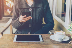 Γυναίκα χεριών που χρησιμοποιεί το smartphone στη καφετερία και το μαλακό φως Στοκ Εικόνα