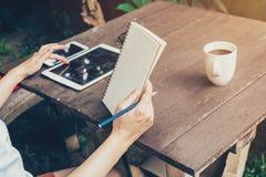 Γυναίκα χεριών χρησιμοποιώντας την ταμπλέτα και κρατώντας το σημειωματάριο στο επιτραπέζιο ξύλο σε ομο Στοκ εικόνες με δικαίωμα ελεύθερης χρήσης