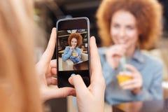 Γυναίκα χρησιμοποιώντας το κινητό τηλέφωνο και παίρνοντας τις φωτογραφίες της φίλης της Στοκ φωτογραφίες με δικαίωμα ελεύθερης χρήσης