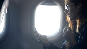 Γυναίκα χρησιμοποιώντας το σύγχρονο smartphone και μιλώντας στο αεροπλάνο φιλμ μικρού μήκους