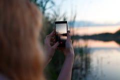 Γυναίκα χρησιμοποιώντας το smartphone και παίρνοντας τη φωτογραφία του ζωηρόχρωμου ηλιοβασιλέματος επάνω από τη λίμνη Στοκ Φωτογραφίες