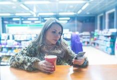Γυναίκα χρησιμοποιώντας app στο smartphone και πίνοντας τον καφέ στον καφέ Στοκ Εικόνες