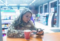 Γυναίκα χρησιμοποιώντας app στο smartphone και πίνοντας τον καφέ στον καφέ Στοκ Εικόνα