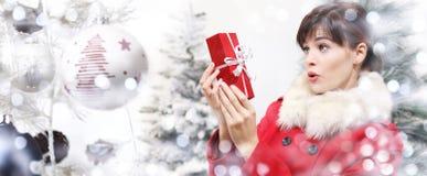Γυναίκα Χριστουγέννων που εκπλήσσεται με τη συσκευασία δώρων στη σφαίρα τ Χριστουγέννων Στοκ Φωτογραφίες