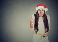 Γυναίκα Χριστουγέννων που διεγείρεται για την απώλεια βάρους που μετρά τη μέση Στοκ εικόνα με δικαίωμα ελεύθερης χρήσης