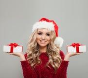 Γυναίκα Χριστουγέννων που φορά το καπέλο Santa που παρουσιάζει δύο άσπρα δώρα Χριστουγέννων Στοκ φωτογραφίες με δικαίωμα ελεύθερης χρήσης