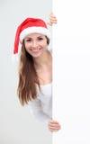 Γυναίκα Χριστουγέννων στο καπέλο santa που κρατά το κενό χαρτόνι στοκ φωτογραφία