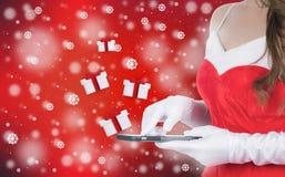 Γυναίκα Χριστουγέννων το έξυπνο τηλέφωνο που στέλνεται που κρατά τα δώρα Χριστουγέννων Στοκ φωτογραφία με δικαίωμα ελεύθερης χρήσης