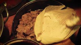 Γυναίκα χρονικού σφάλματος που προετοιμάζει tamale σάλτσας τυφλοπόντικων με το κρέας χοιρινού κρέατος απόθεμα βίντεο