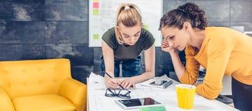 Γυναίκα δύο επιχειρήσεων που ελέγχει τα σχεδιαγράμματα Στοκ Εικόνες