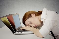 Γυναίκα ύπνου στο γραφείο της, στον υπολογιστή στοκ φωτογραφία