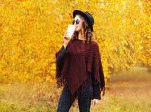 Γυναίκα ύφους φθινοπώρου μόδας η νέα αρκετά με το φλυτζάνι καφέ που φορά τα γυαλιά ηλίου μαύρων καπέλων έπλεξε poncho πέρα από τα Στοκ φωτογραφία με δικαίωμα ελεύθερης χρήσης