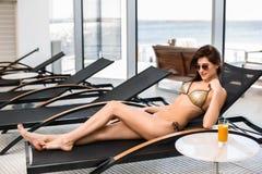 γυναίκα ύδατος σωμάτων care foot health spa Γυναίκα με το τέλειο σώμα στο μπικίνι που βρίσκεται στο deckchair από την πισίνα Στοκ φωτογραφίες με δικαίωμα ελεύθερης χρήσης