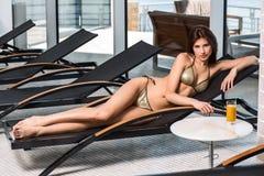 γυναίκα ύδατος σωμάτων care foot health spa Γυναίκα με το τέλειο σώμα στο μπικίνι που βρίσκεται στο deckchair από την πισίνα Στοκ φωτογραφία με δικαίωμα ελεύθερης χρήσης