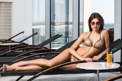 γυναίκα ύδατος σωμάτων care foot health spa Γυναίκα με το τέλειο σώμα στο μπικίνι που βρίσκεται στο deckchair από την πισίνα Στοκ Εικόνες