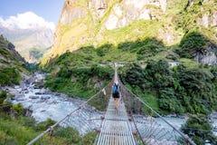 Γυναίκα backpacker που διασχίζει τη γέφυρα αναστολής στα Ιμαλάια Νεπάλ Στοκ Εικόνες