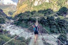 Γυναίκα backpacker που διασχίζει τη γέφυρα αναστολής στα Ιμαλάια Νεπάλ Στοκ Εικόνα