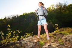 Γυναίκα backpacker που στέκεται και που απολαμβάνει τη θέα στο δάσος Στοκ Φωτογραφία
