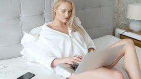 Γυναίκα Beatutiful στην κομψή άσπρη συνεδρίαση πουκάμισων των ανδρών στο κρεβάτι με το lap-top φιλμ μικρού μήκους