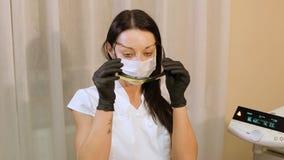 Γυναίκα Beautician ή γιατρών που τίθεται στα προστατευτικά γυαλιά με τα μαύρα λαστιχένια γάντια απόθεμα βίντεο