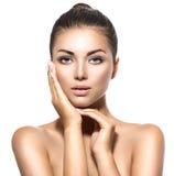 Γυναίκα Beautiful spa brunette σχετικά με το πρόσωπό της Στοκ φωτογραφία με δικαίωμα ελεύθερης χρήσης