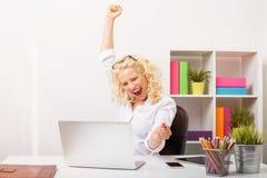 Γυναίκα Beuatifull στο γραφείο που γιορτάζει την επιτυχία της στοκ εικόνες