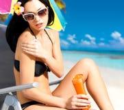 Γυναίκα bikini που εφαρμόζει την κρέμα ομάδων δεδομένων ήλιων στο σώμα Στοκ Φωτογραφία