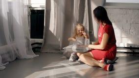 Γυναίκα brunet έχοντας τη διασκέδαση με το κορίτσι, που κάθεται στο πάτωμα στο καθιστικό φιλμ μικρού μήκους