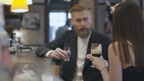 Γυναίκα Brunette και βέβαια ξανθή γενειοφόρος συνεδρίαση ανδρών αντίθετο στενό στον επάνω φραγμών Έννοια του τρόπου ζωής νύχτας r απόθεμα βίντεο