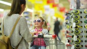 Γυναίκα Brunette με τα μακρυμάλλη γυαλιά ηλίου επιλογής για την λίγη κόρη που στέκεται κοντά στο ράφι Χαριτωμένο κορίτσι με δύο φιλμ μικρού μήκους