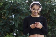 Γυναίκα Brunette που ακούει και που απολαμβάνει τη μουσική στα ακουστικά Στοκ Φωτογραφίες