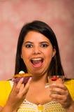 Γυναίκα Brunette που κρατά εύγευστο καφετί χρωματισμένο muffin με το κάλυμμα κρέμας, ποτήρι mousse σε άλλο χέρι, μεγάλο χαμόγελο  Στοκ εικόνα με δικαίωμα ελεύθερης χρήσης