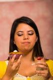 Γυναίκα Brunette που κρατά εύγευστο καφετί χρωματισμένο muffin με το κάλυμμα κρέμας, ποτήρι mousse σε άλλο χέρι, μεγάλο χαμόγελο  Στοκ Εικόνα
