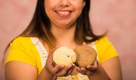 Γυναίκα Brunette που κρατά τα εύγευστα καφετιά χρωματισμένα μπισκότα, μεγάλο χαμόγελο και έτοιμος να πάρει ένα δάγκωμα, έννοια ζύ Στοκ Εικόνες