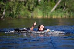 Γυναίκα Brunette που οδηγά wakeboard σε μια θερινή λίμνη Στοκ Φωτογραφίες