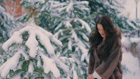 Γυναίκα Brunette που ρίχνει το χιόνι στον αέρα στις χειμερινές διακοπές σε αργή κίνηση φιλμ μικρού μήκους