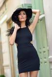 Γυναίκα Brunette που φορά το μαύρο σαγηνευτικό φόρεμα στην οδό Στοκ Φωτογραφίες