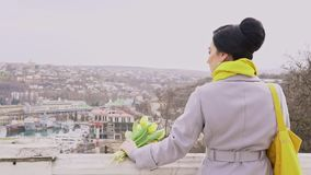 Γυναίκα Brunette στα παλτά με τις κίτρινες τουλίπες φιλμ μικρού μήκους