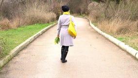Γυναίκα Brunette στα παλτά με τις κίτρινες τουλίπες απόθεμα βίντεο