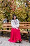 Γυναίκα Brunette στην κόκκινη συνεδρίαση φορεμάτων στον πάγκο στο πάρκο φθινοπώρου στοκ φωτογραφία με δικαίωμα ελεύθερης χρήσης