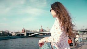 Γυναίκα Brunette στο άσπρο φόρεμα που εξετάζει τη Μόσχα Κρεμλίνο απόθεμα βίντεο