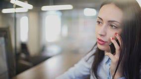 Γυναίκα Brunette στο γραφείο που μιλά στο τηλέφωνο κατά τη διάρκεια του σπασίματος στο εσωτερικό φιλμ μικρού μήκους