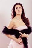 Γυναίκα Brunette στο φωτεινό boa φορεμάτων φτερό Στοκ Φωτογραφίες