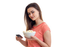 Γυναίκα brunette Prettty που προσέχει τη TV με pop-corn Στοκ Φωτογραφίες