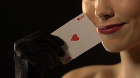 Γυναίκα Flirty που παρουσιάζει άσσο των καρδιών στη κάμερα, έννοια τύχης, χαρτοπαικτική λέσχη πολυτέλειας απόθεμα βίντεο