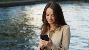Γυναίκα Freelancer που κοιτάζει βιαστικά στο smartphone, που κάθεται ενάντια στο νερό ποταμού φιλμ μικρού μήκους