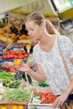 Γυναίκα greengrocers που κρατούν την κίτρινη ντομάτα Στοκ Εικόνα